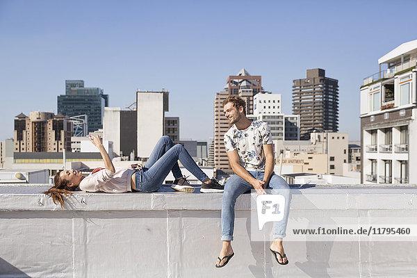 Junges Paar auf der Balustrade einer Dachterrasse mit Smartphone