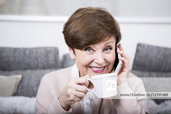 Porträt einer älteren Frau mit Smartphone  Kaffee trinken