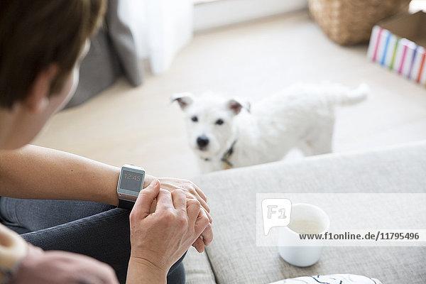 Frau sitzt zu Hause auf der Couch und schaut auf smartwatch