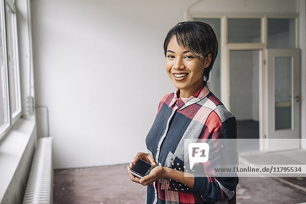 Portrait of smiling young woman holding phablet