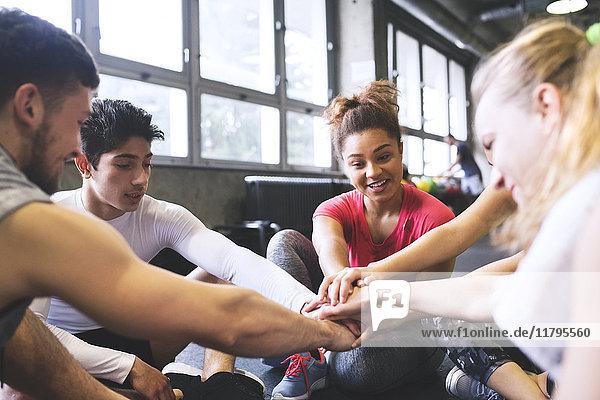 Gruppe junger Leute  die eine Pause machen und sich in der Turnhalle zusammenkauern