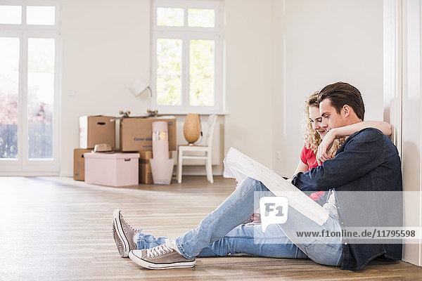 Junges Paar in neuem Zuhause auf dem Boden sitzend mit Blick auf den Grundriss