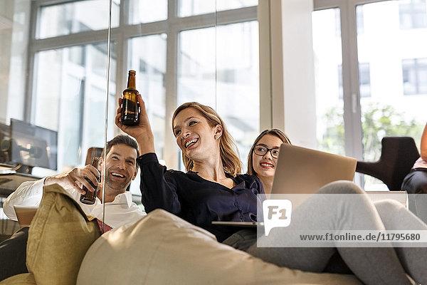 Lässige Geschäftsleute klirren Bierflaschen im Büro