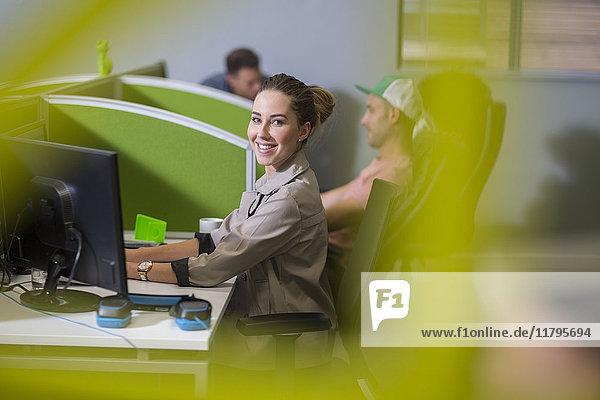 Junge Frau bei der Arbeit am Computer in der Bürozelle