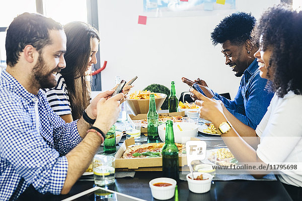 Freunde  die Handys am Esstisch benutzen