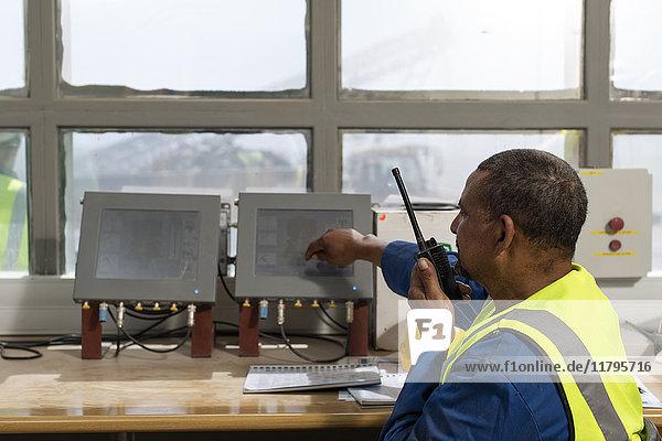 Mitarbeiter im Baustellenbüro beim Sprechen am Funkgerät