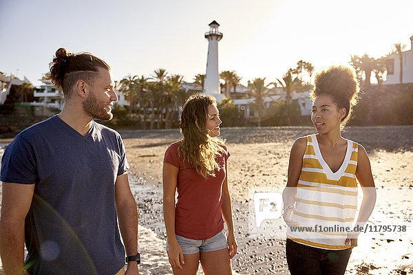 Spanien  Kanarische Inseln  Gran Canaria  drei Freunde beim Strandspaziergang in der Abenddämmerung