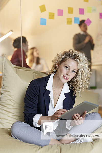 Portrait of woman in office using tablet in bean bag with meeting in background