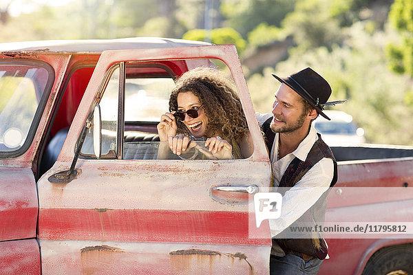 Fröhliches junges Paar beim alten Pickup