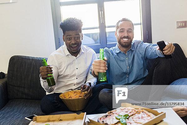 Freunde mit Bierflaschen auf dem Sofa sitzen und fernsehen