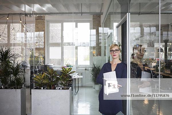 Porträt einer Geschäftsfrau im Amt  die Papiere hält