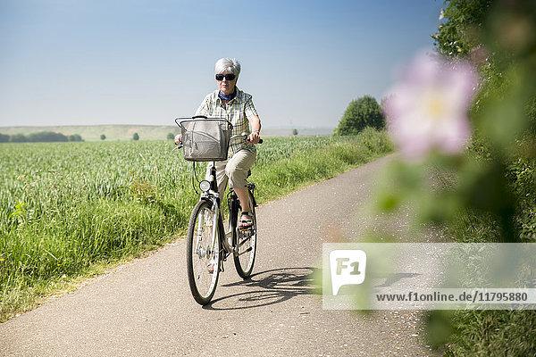 Deutschland  Seniorin beim Radfahren im Sommer