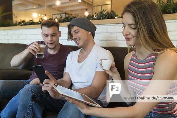 Drei Freunde mit Tablette und Handy in einem Cafe