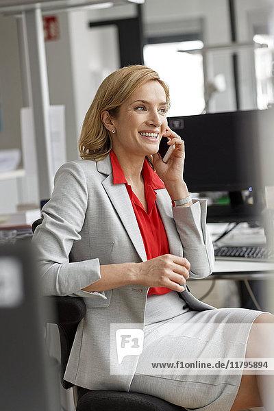 Geschäftsfrau am Schreibtisch im Büro auf dem Handy