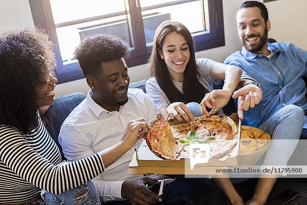 Glückliche Freunde sitzen auf dem Sofa und teilen sich eine Pizza.