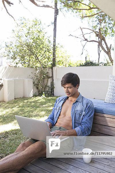 Mann auf der Terrasse im Garten sitzend mit Laptop