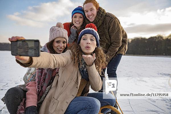 Freunde mit einem Selfie auf dem zugefrorenen See