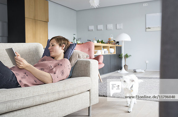 Frau auf der Couch liegend mit Tablette