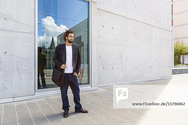 Junger Geschäftsmann mit Rastalocken vor dem Gebäude