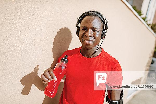 Porträt eines Mannes mit isotonischem Getränk in Sportbekleidung Musik hören mit Kopfhörern