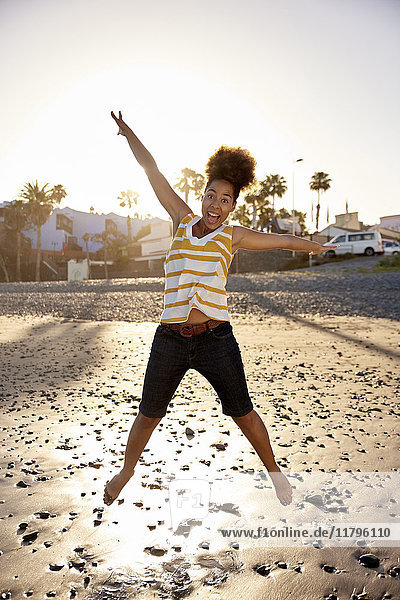 Glückliche Frau  die am Strand in die Luft springt.