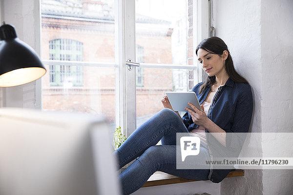 Frau mit Tablette am Fenster im Büro