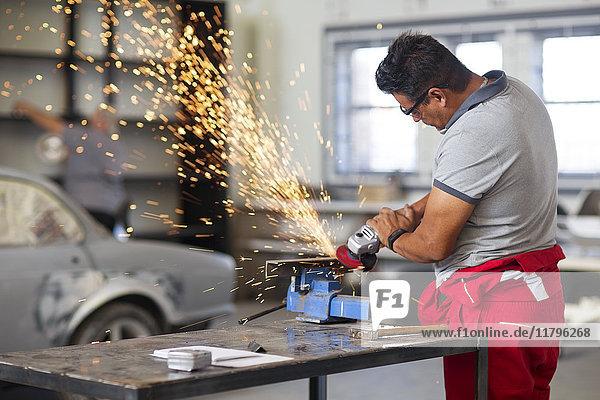 Mechaniker mit Winkelschleifer in der Kfz-Werkstatt