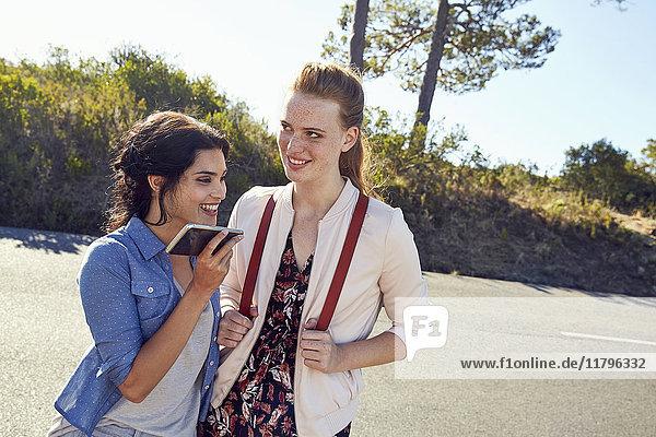 Südafrika  Kapstadt  Signal Hill  zwei lächelnde junge Frauen mit Handy auf Reisen