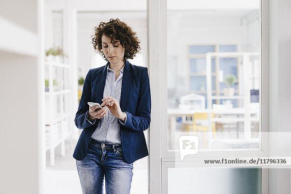 Geschäftsfrau in der Bürotür stehend  mit Smartphone