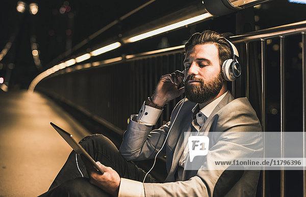 Junger Mann mit Tablette und Kopfhörer  der nachts auf der Brücke sitzt