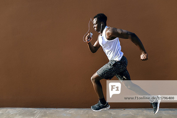Junger Mann rennt vor brauner Wand
