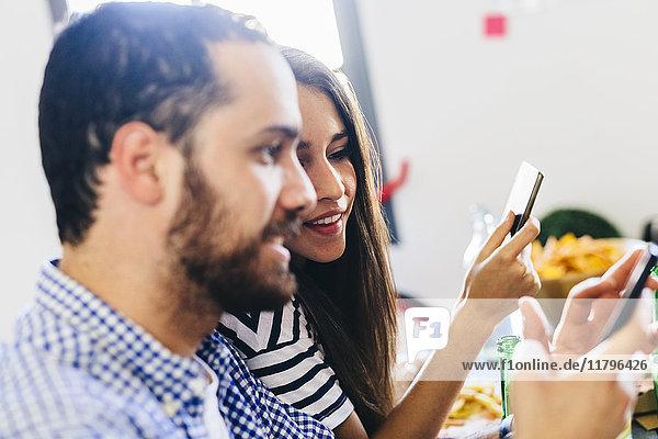 Paar schaut auf Handy am Esstisch