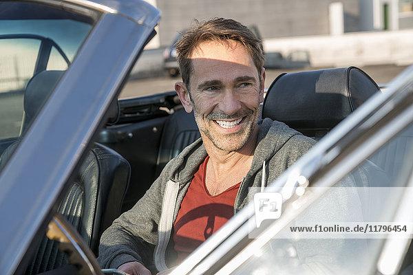 Porträt eines lächelnden reifen Mannes in seinem Sportwagen