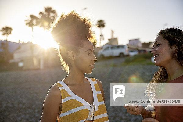Zwei Freunde  die bei Sonnenuntergang am Strand reden.