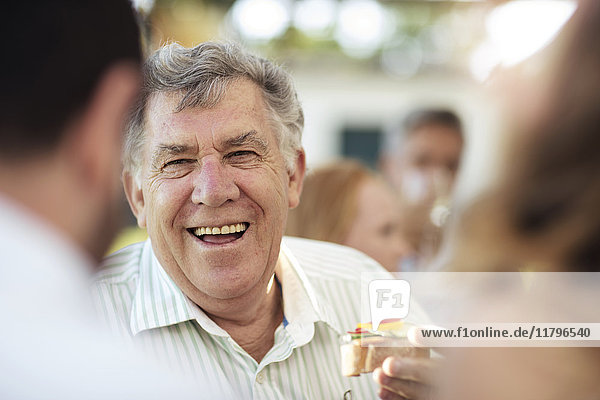 Happy senior man socializing on a garden party