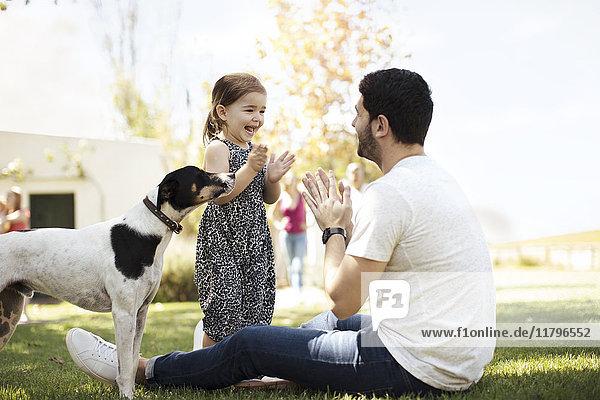 Glücklicher Vater  Tochter und Hund im Garten