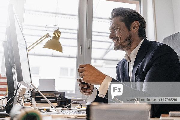 Lächelnder Geschäftsmann bei der Arbeit am Schreibtisch