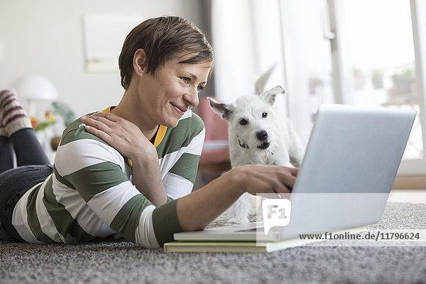 Lächelnde Frau auf dem Boden liegend mit Laptop