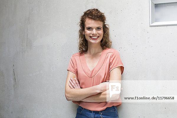 Porträt einer lächelnden Frau  die sich an eine Betonwand lehnt.