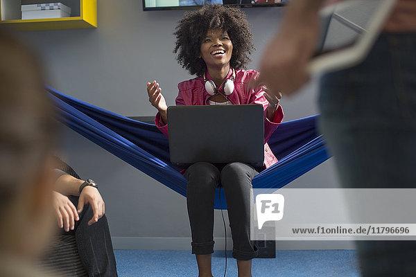 Glückliche Frau in Hängematte mit Laptop