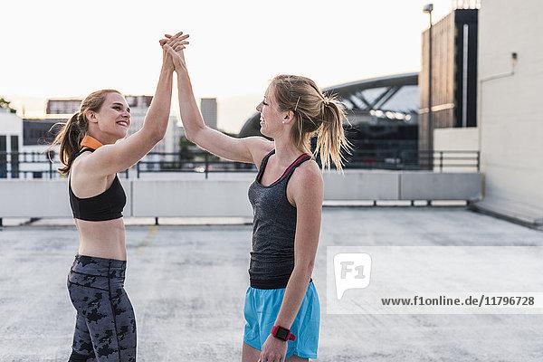Zwei glückliche Frauen,  die eine Pause vom Training auf dem Parkdeck in der Stadt machen