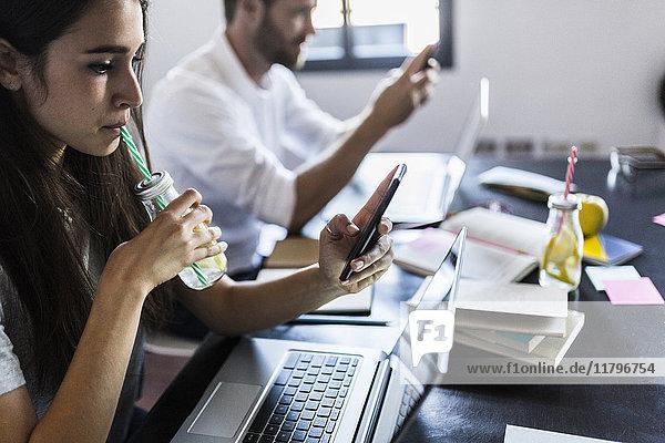 Beschäftigtes Paar zu Hause mit Laptop und Smartphone