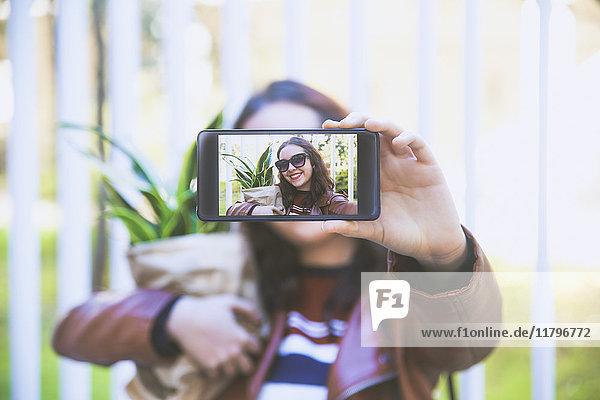 Junge Frau mit Topfpflanze  die Selfie mit Smartphone nimmt