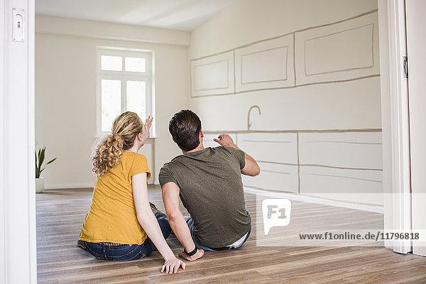 Junges Paar im neuen Zuhause sitzt auf dem Boden und denkt über Innenarchitektur nach.
