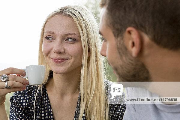 Porträt einer lächelnden blonden Frau mit Espressotasse  beobachtet von ihrem Freund.