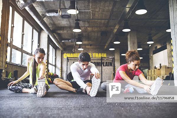 Drei junge Leute  die sich im Fitnessstudio ausstrecken.