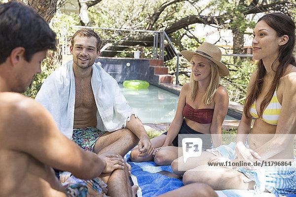 Eine Gruppe von Freunden  die sich im Garten am Pool entspannen.