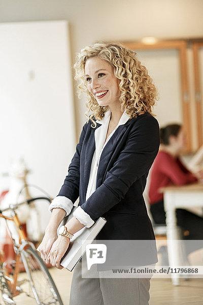 Porträt einer lächelnden Geschäftsfrau mit einer Besprechung im Hintergrund