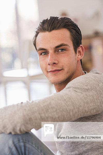 Porträt eines lächelnden jungen Mannes im neuen Zuhause