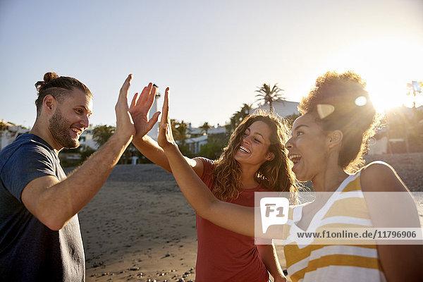 Drei Freunde High Fiving am Strand